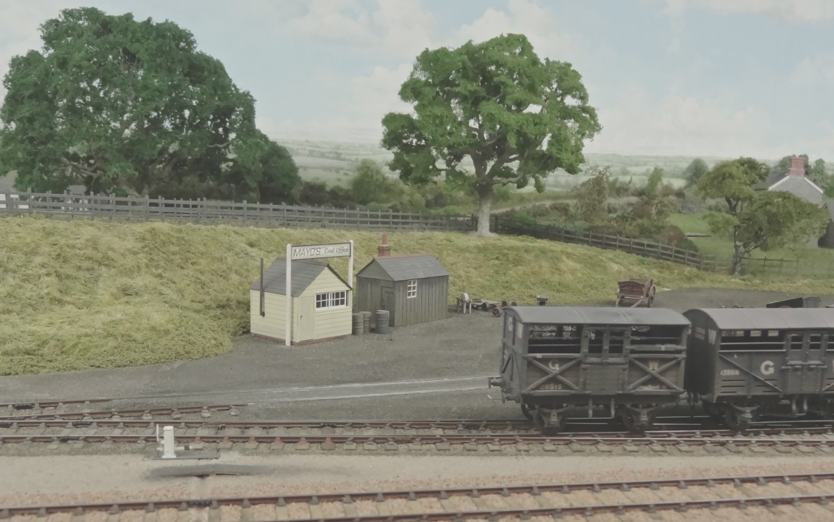 A different overview of the yard approach, with G.W.R. Cattle stock and timber offices in the foreground. Behind the fence, Station Road leads away to the right, north east towards Semley village, Tisbury and Teffont. As it rose up to cross the line, the road then climbed to Shaftesbury, three miles to the south of this point.