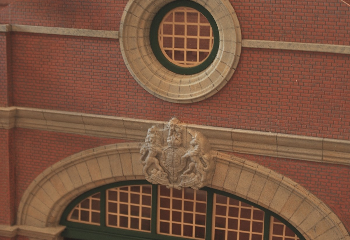 Stone cornices and carved keystone detail. To keep to the generic nature of the station, the coat of arms is simply the royal emblem instead of that of a railway company. The decorative window portal in the gable above was turned to the same profile as the arch below, and the panelled glazing is laminated from plastikard profiles.