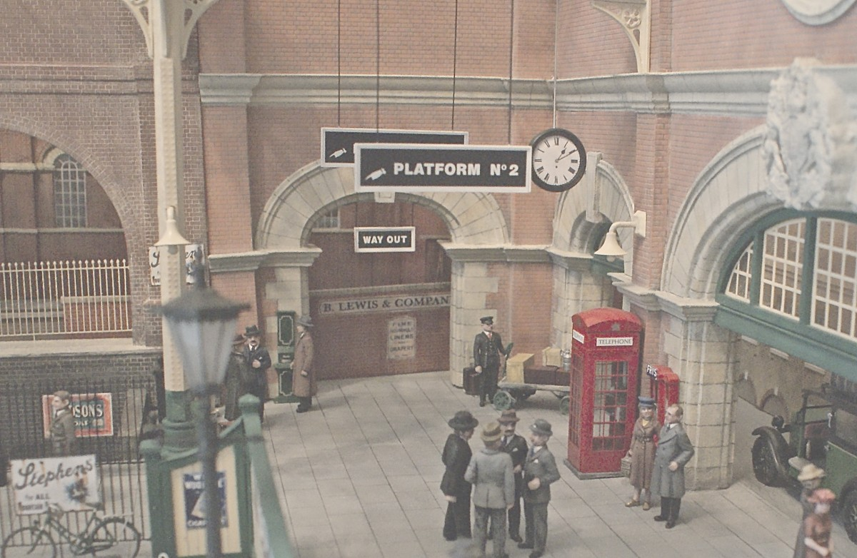 The way out, with a 1930s telephone kiosk and a period vending machine. Groups of passengers wait to continue their journeys.