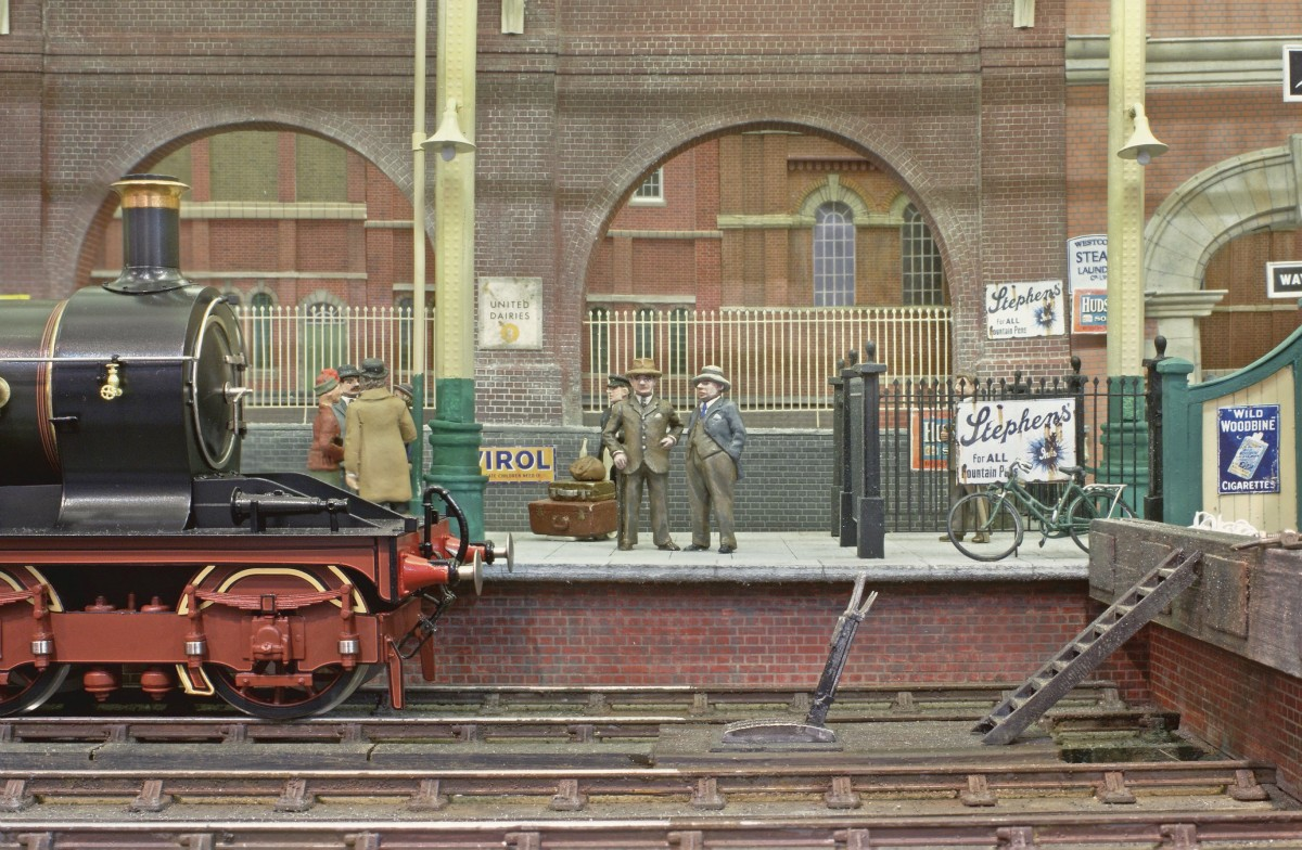 Detail from terminus interior, with platform end clutter, and a parallel one layer backscene at reduced scale. The standing passengers populating the concourse are new releases from Andy Stadden and these additions to his range can now be viewed by clicking the link below. Original by Steve Flint/Railway Modeller.