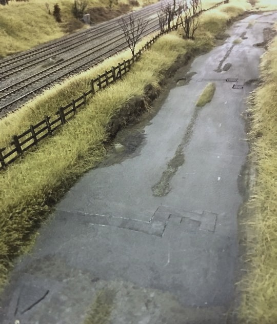 The lineside road is detailed as a poorly maintained thoroughfare, with patched asphalt, potholes and puddles. The shrub trees are bare of leaves, and the scene is bleak and wintry.